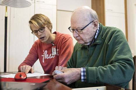 Peik Hämekoski (taustalla) auttaa vanhuksia digipalveluiden ja -laitteiden kanssa.
