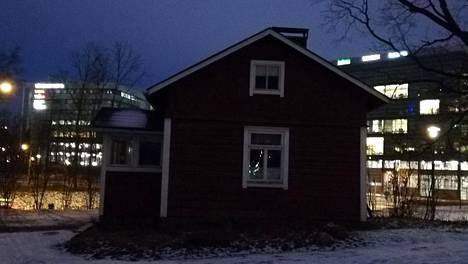Kuvassa taustalla valaistut toimistot. Etualalla näkyy yli 100-vuotias Puutarhurin mökki.