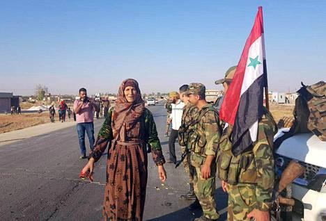 SANA-uutistoimiston julkaisemassa kuvassa syyrialaissiviilit toivottivat hallituksen sotilaat tervetulleiksi näiden saapuessa Tal Tamrin kaupunkiin lähellä Syyrian ja Turkin rajaa.
