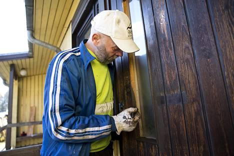 Maalari Eero Hyvärinen työstää Veli Mäkisen tiellä sijaitsevien talojen ovia.