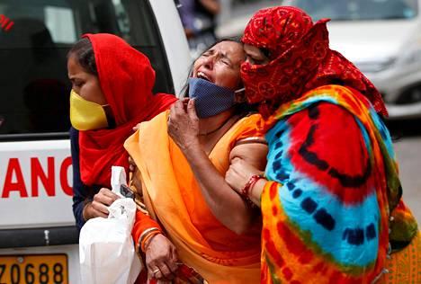 Nainen itkee menetettyään aviomiehensä koronaviruksen aiheuttamalle taudille.