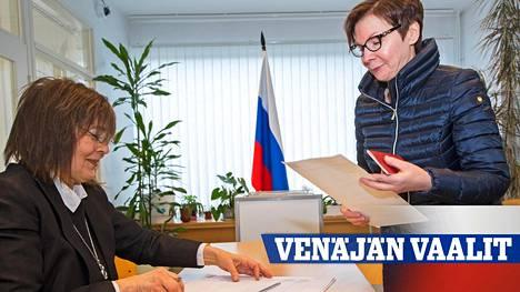Lappeenrannan konsulaatin työntekijä Ljdumila Romanova (vas.) tarkistaa äänestäjien henkilöllisyyden. Vuorossa on kouvolalainen Ingrid Lehikoinen.