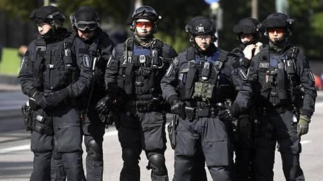Poliisit valvoivat Pakkopalautukset Afganistaniin seis -mielenosoitusmarssia Helsingissä 14. syyskuuta.