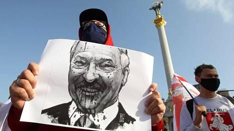 Mielenosoittaja piteli pilakuvaa Lukashenkasta.