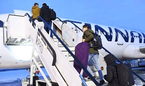 Matkustajia nousemassa Finnairin lennolle Kuusamon lentokentällä joulukuussa 2019.