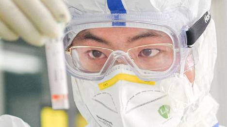 Laboratoriotyöntekijä suoritti koronavirustestejä Wuhanissa torstaina.