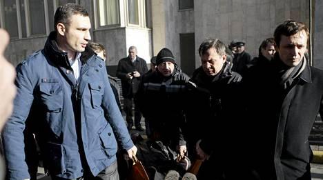 Oppositiojohtaja Vitali Klitshko (vas.) kantoi mellakoiden uhria paareilla.