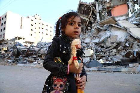 Palestiinalaistyttö käveli Hamasin hallitsemassa Gazassa kadulla, jonka varrelta Israelin ilmaisku tuhosi aiemmin rakennuksen.