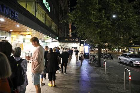 Ihmisiä jonottamassa muumimukeja yöllä Helsingissä.