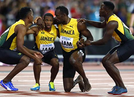 Yohan Blake (toinen vas.) ja Omar McLeod (oik.) auttoivat Usain Boltin ylös.