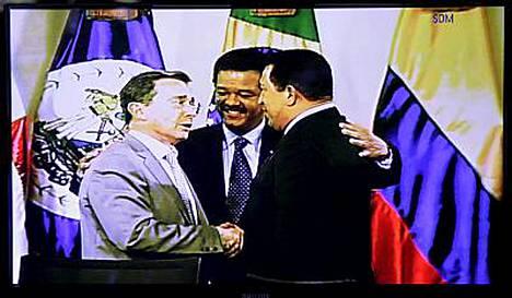 Kolumbian presidentti Alvaro Uribe (vas.) ja Venezuelan presidentti Hugo Chavez (oik.) kättelevät sovinnon merkiksi. Keskellä Dominikaanisen tasavallan presidentti Leonel Fernandez.