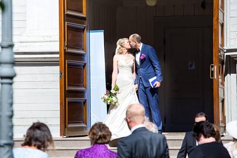 Pari vaihtoi keskenään herkän suudelman kirkon edessä.