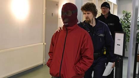 Syytetty mies saapui Oulun käräjäoikeuteen perjantaina poliisin huostassa tummanpunainen naamio päässään.