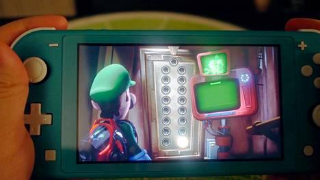 Nintendo Switch Lite -konsolista on karsittu tv-ominaisuudet edullisimman hinnan ja kevyemmän rakenteen tieltä. Kuvassa laitteella kokeillaan Luigi's Mansion 3 -peliä.