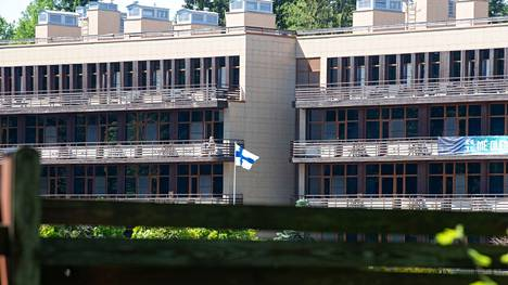Suomen hotelli on tiukasti aidattu. Lippu liehuu keskellä pihaa.
