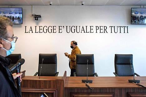 """""""Laki on sama kaikille"""", lukee väliaikaisessa oikeussalissa seinällä suomeksi käännettynä. Etualalla tuomareiden istumapaikat."""