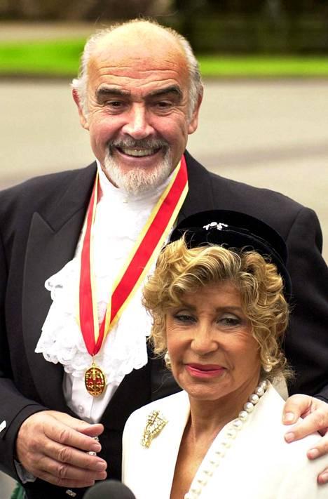 Vuonna 2000 Connery aateloitiin. Tuore Sir Sean Connery hymyili kameroille saapuessaan kuningatar Elisabetin luota vaimonsa Michelinen kanssa.