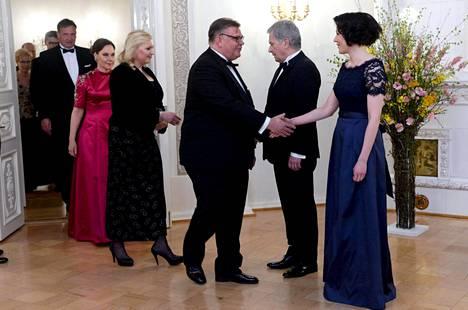 Rouva Jenni Haukio pukeutui tyylikkääseen tummansiniseen iltapukuun. Kättelyvuorossa ulkoministeri Timo Soini puolisoineen.