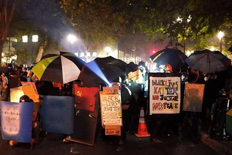 Mielenosoittajat suojautuivat sateenvarjoilla ja omatekoisilla kilvillä.