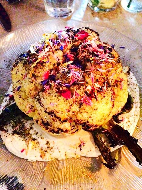 Ravintola Holidayn kukkakaali on viimeistelty syötävillä kukkien terälehdillä. Tahinikastike on kukkakaalin alla dippausta varten.