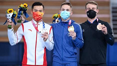 Ivan Litvinovitsh (keskellä) voitti olympiakultaa. Dong Dong (vas.) oli kisassa toinen ja Dylan Schmidt kolmas.