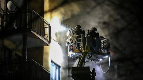 Paineilmalaitteilla varustautuneita poliiseja tarkastamassa palavaa asuntoa.