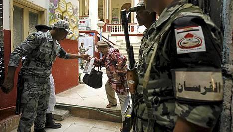 Egyptin turvallisuusjoukkojen sotilas tarjosi auttavan kätensä sunnuntaina äänestämässä käyneelle rouvalle.