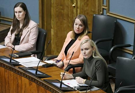Sanna Marin Katri Kulmunin ja Maria Ohisalon kanssa eduskunnan täysistunnossa 24. maaliskuuta 2020.