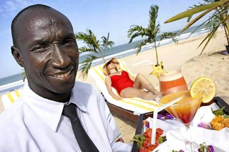 Gambialaisella hiekkarannalla maistuu usein drinkki ja seura. Kuvan henkilöt eivät liity juttuun.