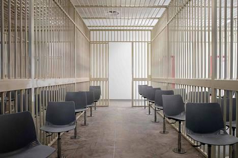 Syytetyt seuraavat käsittelyä oikeussaliin pystytetyissä häkeissä istuen.
