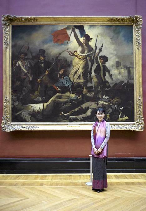 """Johtaako vapaus myös Burmaa? Tässä uutiskuvassa on tietynlaista symboliikkaa. Burman oppositiojohtaja Aung San Suu Kyi seisoo Eugene Delacroix'n kuuluisan Vapaus johtaa kansaa –maalauksen edessä Louvren museossa Pariisissa. Jos teos maalattaisiin nyt, olisi Burman demokratian puolesta taisteleva Suu Kyi oiva esikuva """"vapauden lippua kantavalle naiselle"""". Suu Kyi on aktiivisesti vastustanut Burmaa hallitsevaa sotilasjunttaa ja on päättänyt olla luovuttamatta ennen kuin maa siirtyy täyteen demokratiaan. Suu Kyin kotimaan viranomaiset ovat vaatineet, että oppositiojohtaja puhuu valtiosta sen virallista nimeä käyttäen. Suu Kyi käyttää sotilashallituksen Myanmariksi nimeämästä maasta sen aiempaa nimeä Burma. Suu Kyi vieraili Ranskassa viiden maan Euroopan-kiertueensa päätteeksi."""