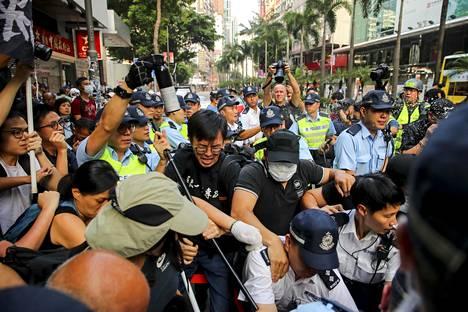 Poliisit yrittivät estää mielenosoittajien joukkoa etenemästä.