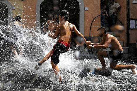 Vesisotaa. Pojat leikkivät kadulla virtaavassa Tenza-joen vedessä Campagnan kylässä eteläisessä Italiassa. Kylässä johdettiin joen vettä kaduille jo 1200-luvulla, jotta kadut saatiin puhdistettua eläinten jätöksistä. Tuo perinne jatkuu yhä. Kerran vuodessa vesi virtaa 12000 asukkaan kylän kaduilla ja lapset voivat leikkiä vesisotaa vuosittaisen La Chiena -tapahtuman aikana.