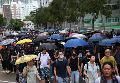 Mielenosoittajat olivat varustautuneet säätilaan sateenvarjoin lauantaina.