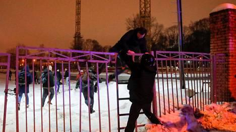 Mielenosoittajat pakeneva poliiseja Moskovassa Aleksei Navalnyin vankilan edustalla, jonne he tulivat vaatimaan Navalnyin vapauttamista.