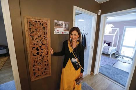 Designtalo Airon Neidon sisustuksen suunnittelija Tiina Henttonen esittelemässä käytännöllistä pyykkikuilua. Pyykkikuilun ovi on Indonesiasta.