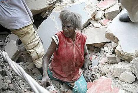 Pelastustyöntekijät auttoivat naista turvaan raunioista Port-au-Princessä.