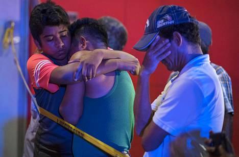 Ihmiset lohduttivat toisiaan tuhoisan iskun jälkeen.