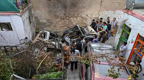 Ihmiset arvioivat droneiskun aiheuttamia tuhoja.