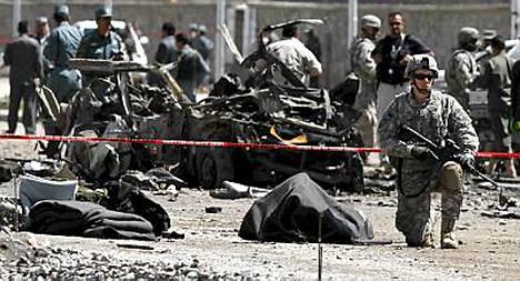 Yhdysvaltain sotilas vartio peitetyn ruumiin vieressä itsemurhapommittajan iskupaikalla tiistaina.