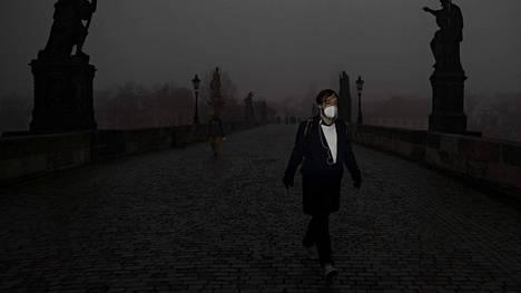 Maskia käyttävä mies kävelee Kaarlensillalla Prahassa 24. helmikuuta 2021.