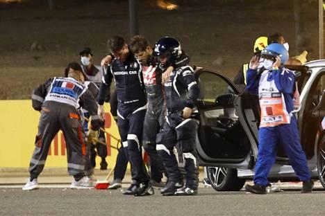 Henkilökunta auttoi tokkuraisen Romain Grosjeanin ambulanssiin.