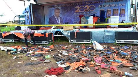 Paikallinen toimittaja tutki ihmisiltä jääneitä kenkiä ja muita tavaroita sen jälkeen, kun ainakin 20 ihmistä oli saanut surmansa ryntäyksessä Ushirikan stadionilla Tansanian Moshissa.