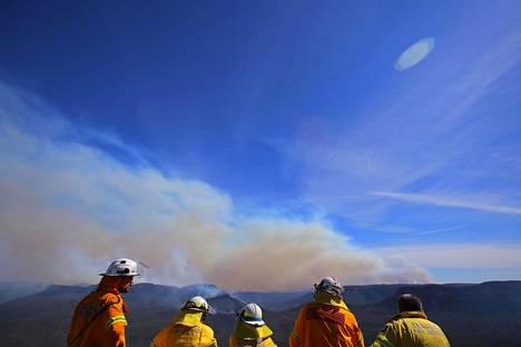 Pelastushenkilöt katselivat maastopaloista nousevaa savupilveä.