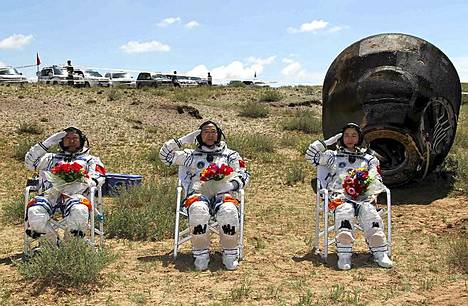 Sankarit tuoleillaan. Kiinalaiset taikonautit Liu Wang, Jing Haipeng ja Liu Yang tervehtivät valokuvaajia Shenzhou 9 -aluksensa laskeutumiskapselin edessä Luoteis-Kiinan Siziwangissa. Shenzhou 9 -alus palasi Maahan historialliselta lennoltaan. Kiinassa avaruusaluksen lähes kahden viikon mittaista matkaa on seurattu tarkasti. Kyseessä oli ensimmäinen kerta, kun kiinalainen miehitetty avaruusalus telakoitui avaruusmoduuliin. Lisäksi lennolla oli ensimmäistä kertaa mukana naispuolinen taikonautti. Kiina tavoittelee pysyvää avaruusasemaa vuoteen 2020 mennessä.