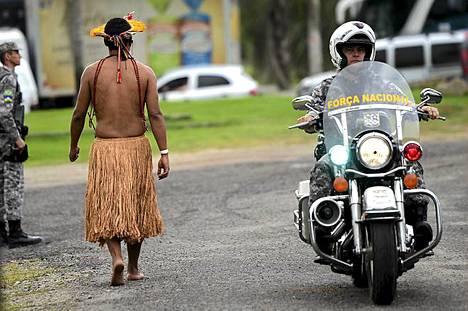 Brasilian alkuperäisasukas kävelee poliisien vartioimalla kadulla Rio de Janeirossa YK:n Rio 20-ympäristökokouksen aikana. Alkuperäiskansat luovuttavat kokouksen yhteydessä Kari-Oca II -nimellä tunnetun julistuksensa maailman päättäjille. Yli 500 alkuperäiskansoihin kuuluvaa ihmistä eri puolilta maailmaa on saapunut kaupunkiin allekirjoittamaan julistuksen. Julistuksessa vaaditaan muiden muassa kunnioittamaan alkuperäiskansojen roolia ympäristön säilyttämisessä ja sitoutumista ekologiseen kehitykseen, ihmisoikeuksiin ja äiti maan oikeuksiin. Rio 20 -kokousta, on jo ehditty arvostella kovin sanoin. Neuvottelujen loppuasiakirjasta päästiin sopuun jo ennen kokouksen alkua, ennen kuin valtioiden päämiehet edes saapuivat paikalle. Arvostelijoiden mukaan asiakirja on riittämätön. Alkuperäinen Rion ilmastokokous pidettiin vuonna 1992.