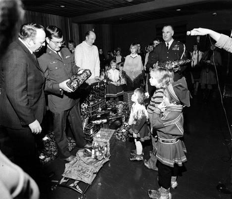 """Operaatio Kulkunen toi jouluiloa Riutulan lastenkotiin 1973. Yhdysvaltain ilmavoimien viestipääesikunnassa palvelleet keräsivät varat lahjoihin myyjäisillä Wiesbadenissa Saksassa myymällä mm. 2000 litraa viiniä. """"Antilta meni sormi suuhun kapteeni Richard Coxin tavatessa nimiä"""", kertoi kuvateksti."""