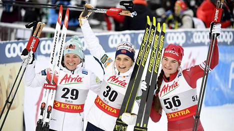 Lauantain kärkikolmikko Therese Johaug (kesk.), Krista Pärmäkoski (vas.) ja Natalia Neprjajeva poseerasivat iloisina kameroille kisan jälkeen.