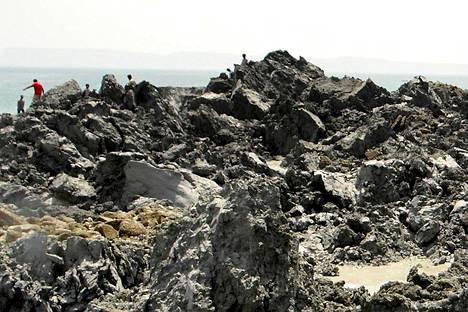 Paikalliset miehet tutkivat saaren kivistä maastoa keskiviikkona.