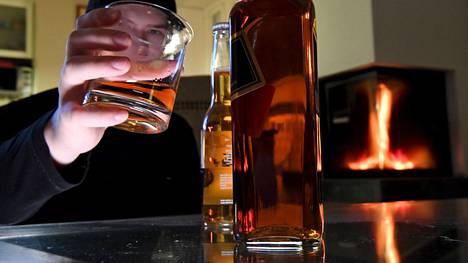 Mies nauttii viskiä kotonaan. Viskipullo ja olutpullo pöydällä.